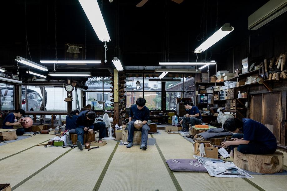 工房の様子。座る姿勢ですら、それぞれがやりやすい体制を取って行うため、ケヤキの木で出来た上がり盤の上に座る職人もいれば、畳の上に座る職人もいる。