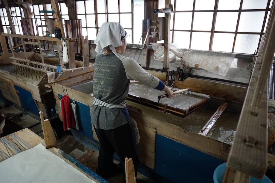 紙漉き。漉き舟(すきふね)に取り付けられている簀桁(すけた)に原料液を汲み込み、中腰で全身の力を使いながら縦横に揺すり、原料液に含まれる繊維同士が絡み合わせることで丈夫な和紙が生まれる。想像以上に大変な作業だが、幾人もの人によって受け継がれてきた大切な漉き技術を継承している。