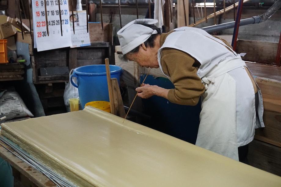 紙床(しと)に重ねられた和紙に気泡ができてしまうため、一つ一つストローを用いて吸い取る。受け継がれてきた大州和紙の質を下げないために、細部への手間を惜しまない気概を感じられる。