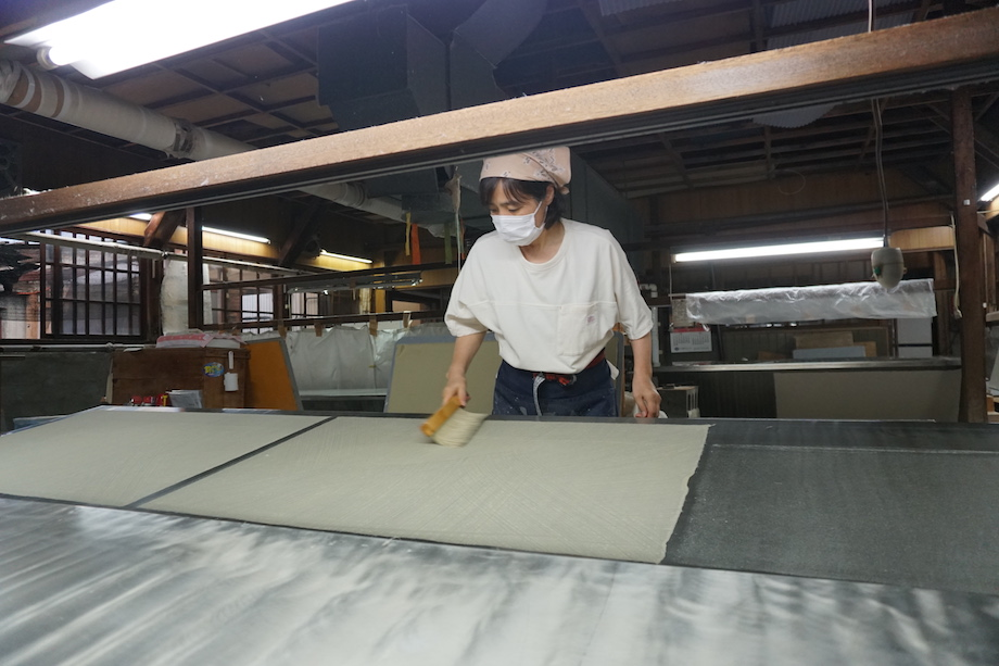 紙漉きの工程を終えた和紙は、圧搾機という機械で和紙に含まれる水を絞り出す。その後、和紙を乾燥機の上に一枚一枚貼り付けていく。その際に、馬刷毛(うまばけ)を用いながら、乾燥機と紙の間に空気が入らないように、また、シワにならないように丁寧に撫でながら貼り付ける。