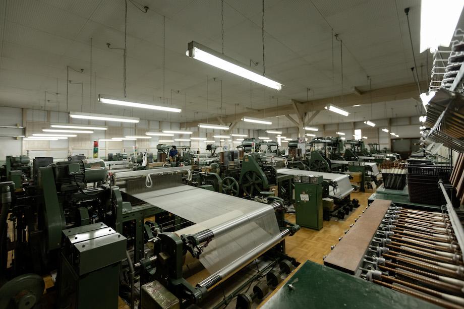 自働織機が並ぶ工場内。部屋いっぱいに、ズラリと並ぶ織り機は60台ほど。数もさることながら、工場内に入った瞬間にその大きな音に圧倒される。
