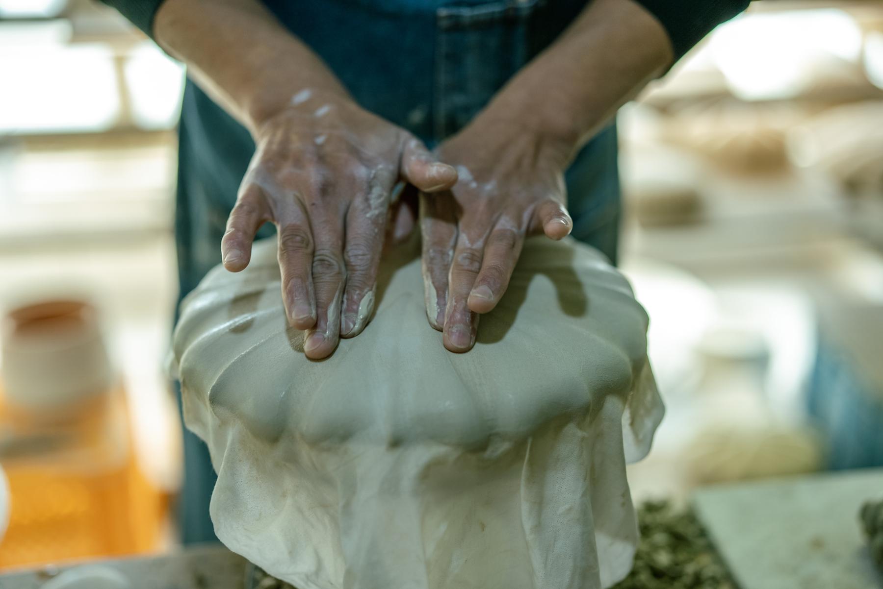 薄く伸ばした素地を石膏の型に被せて手で押し付け、輪花や花弁などに型取ったり、型に彫り込んだ模様をうつわに写し取る成形技法「型打ち」の様子。指で一つ一つ模様に沿わせながら形をつくっていく。